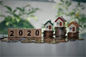 Wooden block year 2020 and mini house on stack coins using as business and financial concept