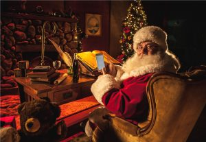 Santa holds a smartphone at his desk with Christmas decor in the background